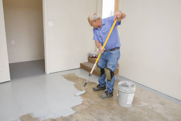 guy painting the concrete of his garage floor